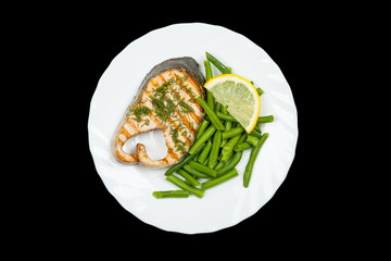 plate of grilled salmon steak isolated on black background