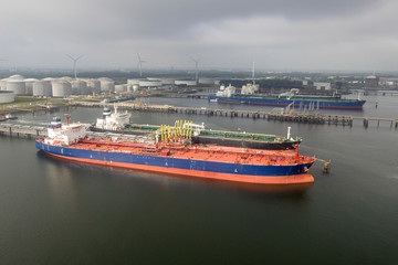 Oil tankers moored at a petrochemical terminal in a large port.