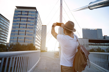 A young hipster in fedora hat and white t-shirt carrying a brown backpack takes a photo of an office building from a bridge on a summer evening.