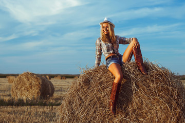 Lovely fashion woman in cow girl country style on hay stack