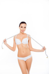 Attractive healthy slim woman in lingerie holding measuring tape