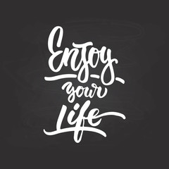 Enjoy your life- hand drawn lettering phrase isolated on the chalkboard background. Fun brush ink inscription for photo overlays, greeting card or t-shirt print, poster design