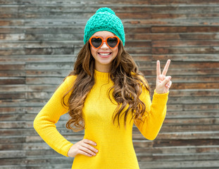 Beautiful smiling brunette woman in sunglasses and knitted  cap