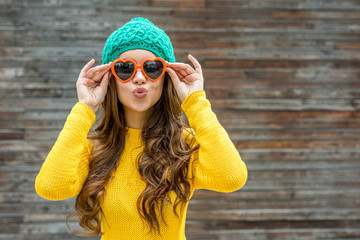 Beautiful brunette woman in sunglasses and knitted  cap blowing
