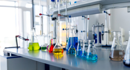 Laboratory table piled tubes with colored liquid, colored reagents in flasks and test tubes