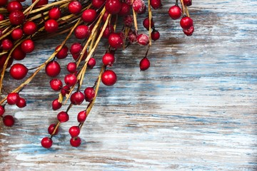 Red Berries on blue wooden background / Christmas background, selective focus