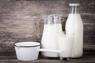 Milch in Krug, Flasche, Stieltopf und Glas auf Holz Hintergrund.