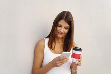 frau steht mit einem kaffeebecher in der stadt und schaut auf ihr handy