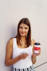 lächelnde junge frau mit kaffee und smartphone