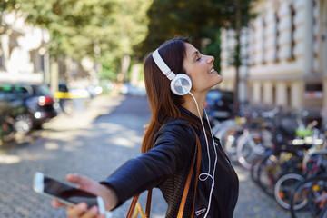 glückliche frau hört musik und tanzt auf der straße