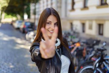 glückliche frau steht auf der straße und zeigt das peace-zeichen mit der hand