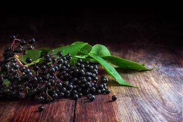 black elderberries (Sambucus nigra) with leaves on a dark wooden background