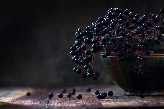 Black elderberries bunch (Sambucus nigra) in an old clay bowl, rustic wood, dark background