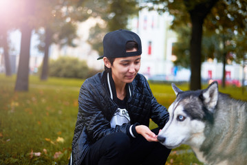 Girl feed the dog in the autumn park. Walking concept. Asian in black cap and coat. Urban style wih sun reflection.