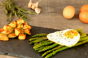 Foto: Asparagus with egg and potatoes with rosemary on a slate dish.