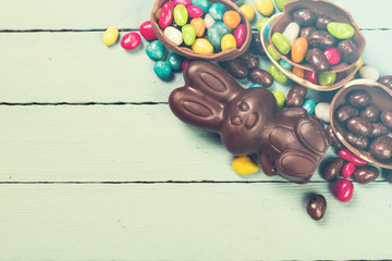 Chocolate Easter eggs and rabbit , on wooden background