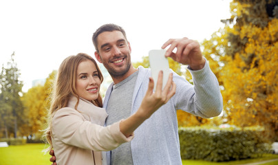 happy couple with smartphone taking selfie in park