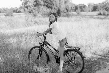 Black and white image of teenage girl riding bicycle at meadow