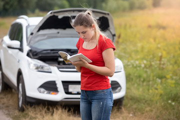 Portrait of stressed woman standing at broken car and reading ow