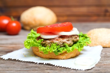 Juicy homemade hamburger with fresh vegetables in table. selective focus