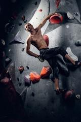 Man climbing on an indoor climbing wall.
