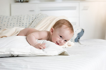 Sdorable baby boy crawling on big bed at bedroom