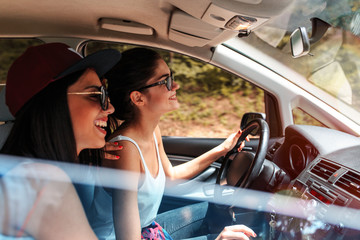 Two young women on car trip.They are driving the car and making fun.Positive emotions.