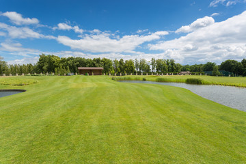 Beautiful golf course with perfect grass and water hindrance at