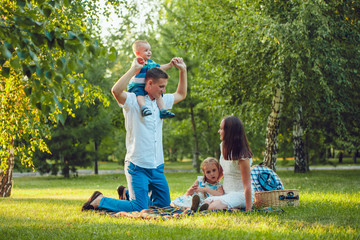 Young happy family of four on picnic in the park and father holding his son  shoulders