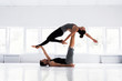 Couple practicing acro yoga in white studio. Acro yoga concept.