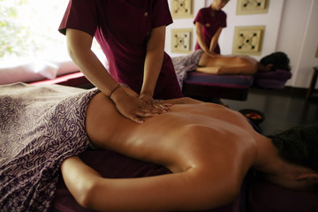 Couple receiving massage at tropical spa