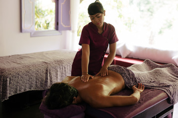 Masseuse giving back massage to man at spa
