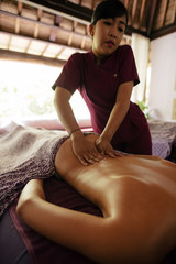 Woman receiving back massage at spa resort