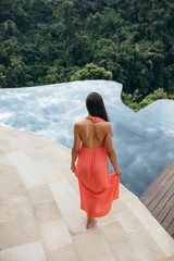 Rear view of woman standing at poolside in tropical resort