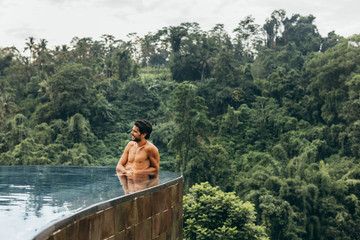 Young man relaxing in infinity poll in tropical landscape