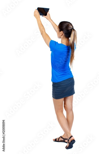 8dbfeca3b9f6 back view of standing young beautiful woman using a mobile phone. Isolated  over white background. girl in a short skirt and a blue T-shirt makes a  selfie on ...