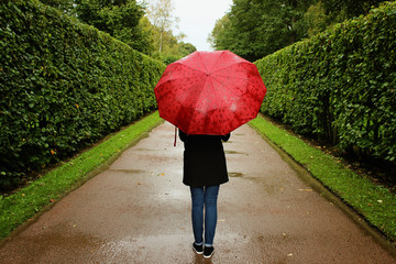 young girl walks along the green alleys from the bushes in the rain with a red umbrella
