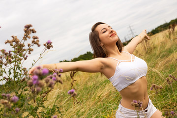 young woman in a field enjoying the fresh air