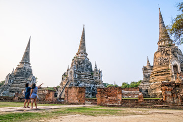 Tourists mother and daughter photography ancient ruins and pagoda of Wat Phra Si Sanphet Temple famous attractions at Phra Nakhon Si Ayutthaya Historical Park in Ayutthaya Province, Thailand