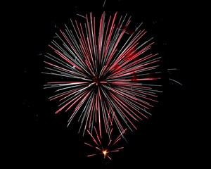 Red and white fireworks fill the sky on the 4th of July