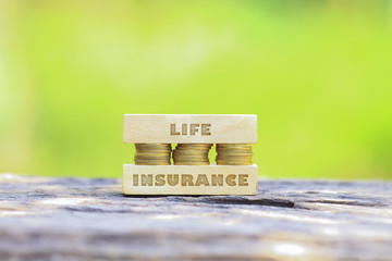 Business Concept - LIFE INSURANCE WORD, Golden coin stacked with woooden bar