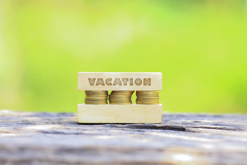 Business Concept - VACATION WORD, Golden coin stacked with wooden bar