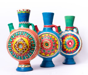 Still life of three decorated colorful handcrafted pottery jugs