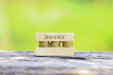 Business Concept - HOBBY WORD, Golden coin stacked with wooden bar