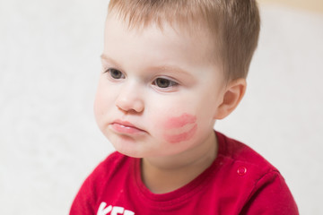 a child with a lipstick kiss on the cheek