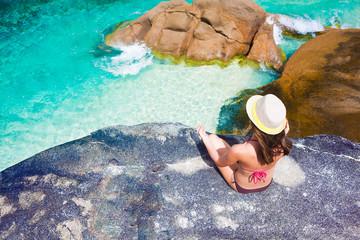 beautiful long haired woman in bikini relaxing on the rocks over the sea. Mahe Islan, Seychelles
