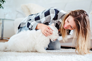 Girl playing with her white cat