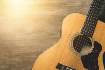 Acoustic guitar on vintage wooden background with sunlight effect filter.