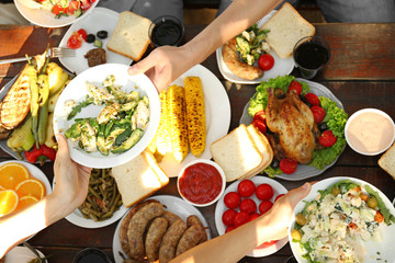 Friends passing plate with tasty salad on picnic