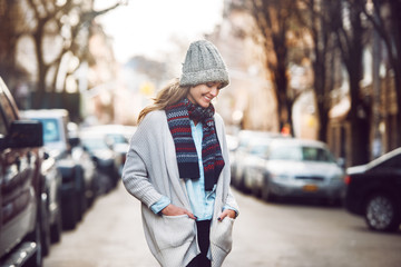 Happy young adult woman walking at beautiful autumn city street wearing colorful scarf and warm hat..